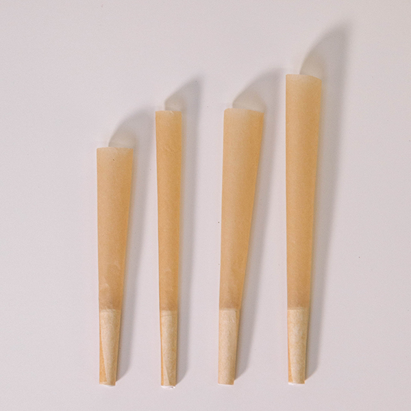 four unrefined brown pre-rolled cones lying on a white background
