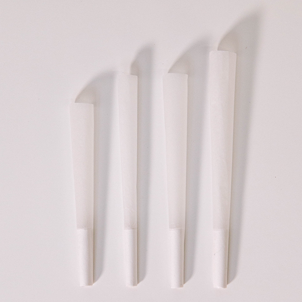 four refined white pre-rolled cones lying on a white background